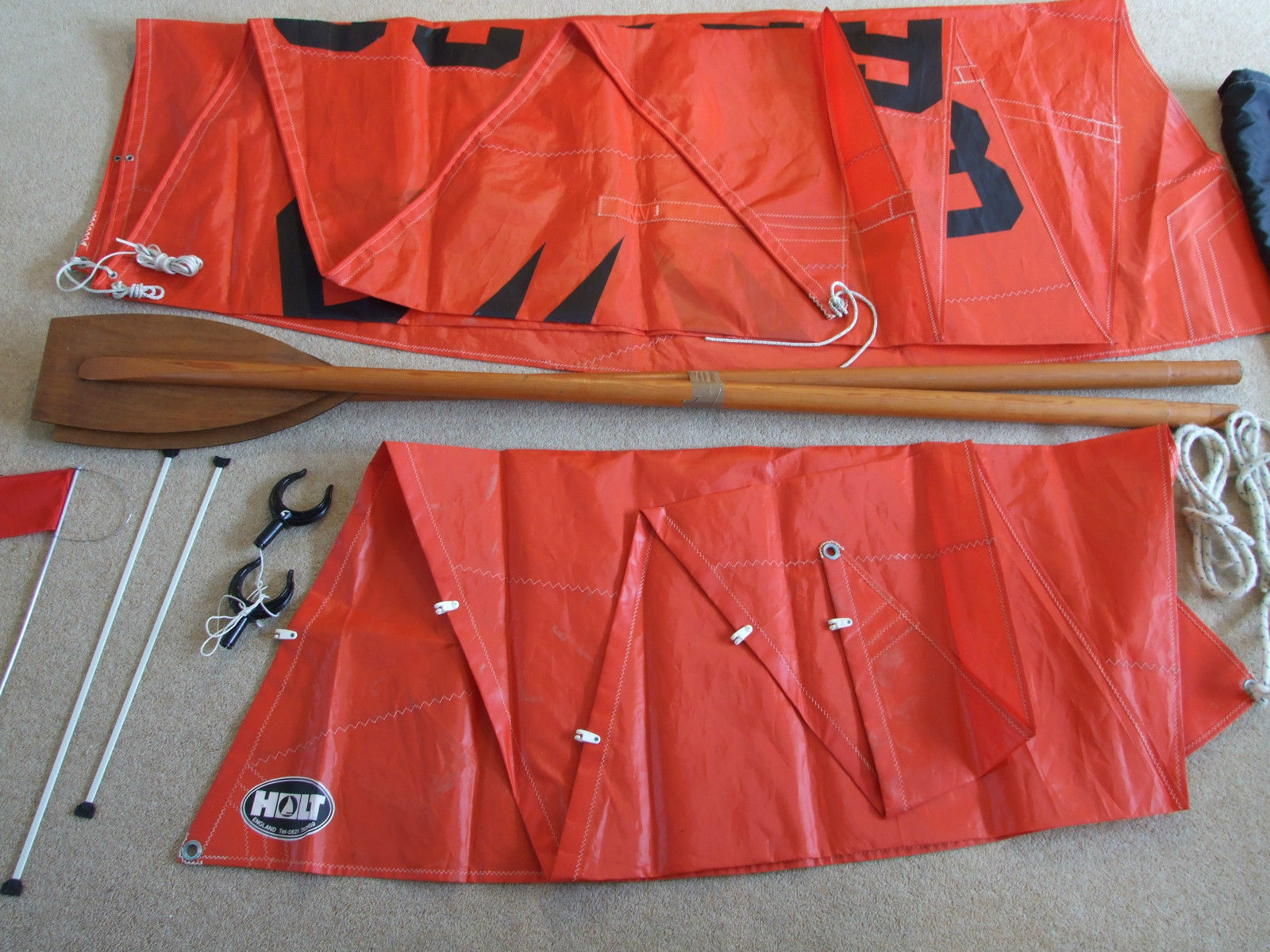 A pair of Mirror oars plus some rowlocks, folded sails, sail battens and a burgee laid out on a carpet