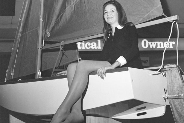 A female model sitting in the back of a Mirror dinghy at the 1968 boat show