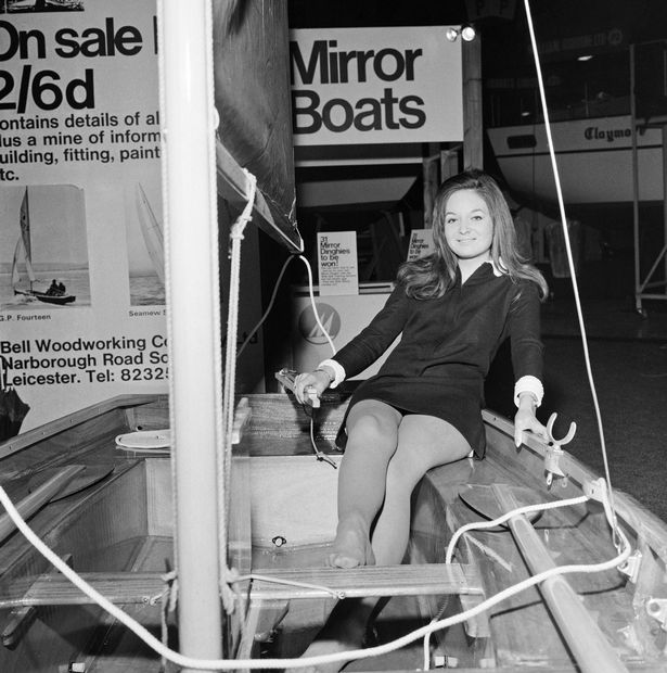 A Mirror dinghy with a female model sitting in it, veiwed from the aft quarter