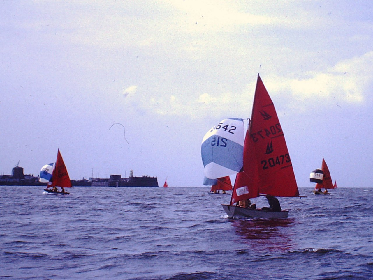 A fleet of Mirror dinghies running down to finish a race