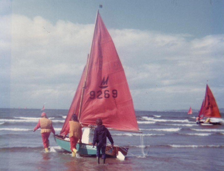 A green wooden Mirror dinghy being lauched into small surf by sailors wearing red waterproof suits and yellow boots