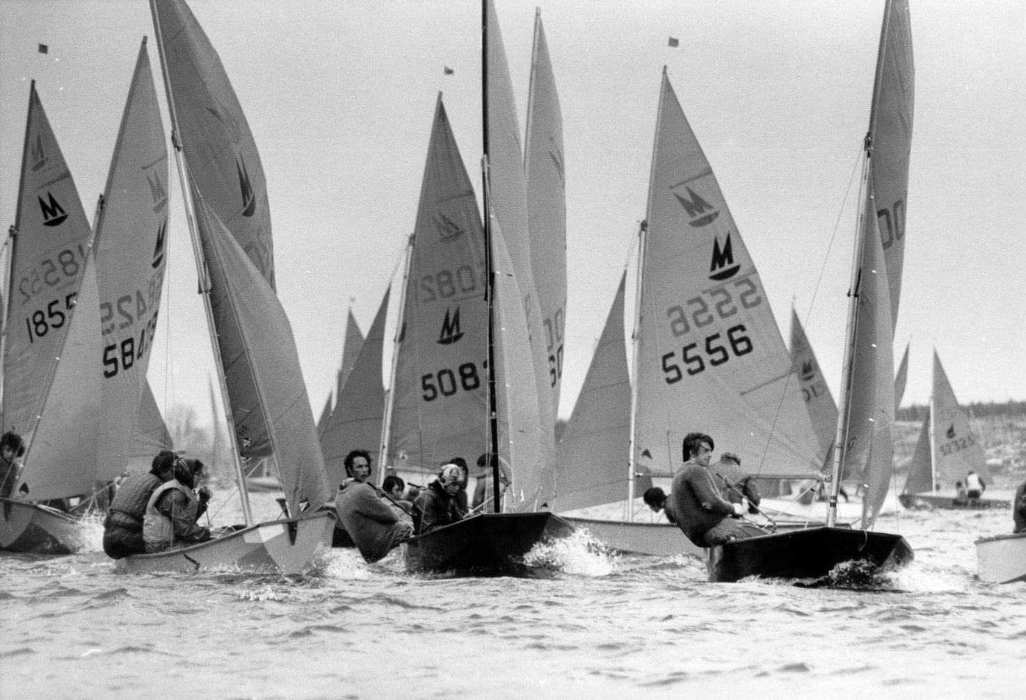Mirror dinghies racing neck and neck about to round a mark