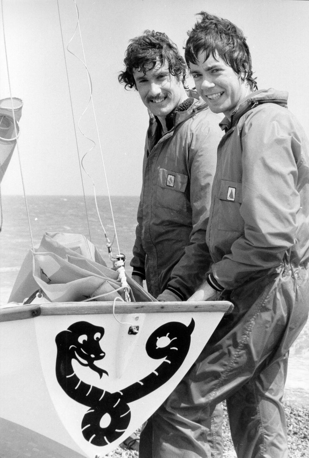 Two teenagers standing next to their Mirror dinghy which has a sidewinder snake painted on the bow transom