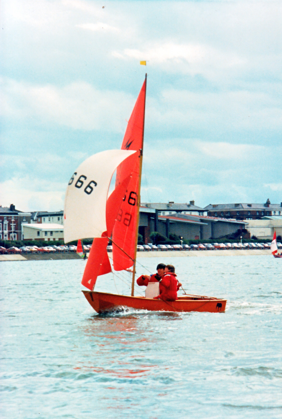 An orange Mirror dinghy with an elephant outline on the rear quarter running downwind with spinnaker set