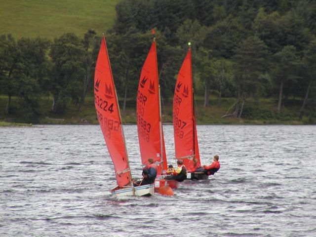 Three Mirror dinghies racing away from the leeward mark and away from the camera