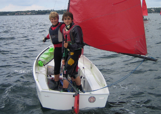 A white Mirror dinghy lying-to with helm & crew looking aft and smiling at the camera