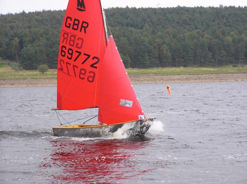 Mirror dinghy sailing upwind on a grey day