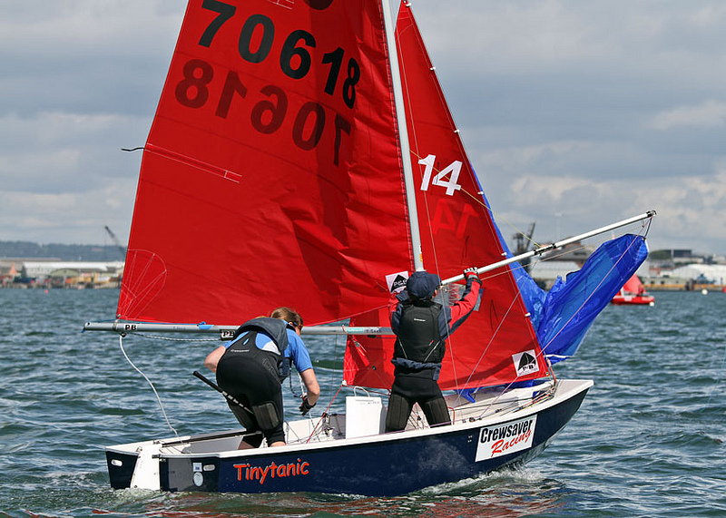 Mirror dinghy with helm hoisting the spinnaker and crew pushing out the pole