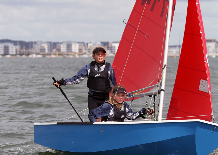 Two girls completing a tack in their Mirror dinghy with the helm standing up