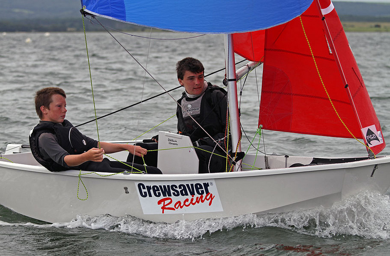 White GRP Mirror dinghy being sailed downwind with the spinnaker up