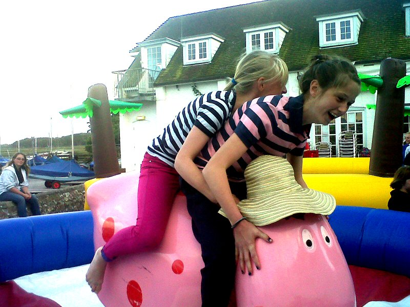 Two girls on a mechanical Ermmintrue cow