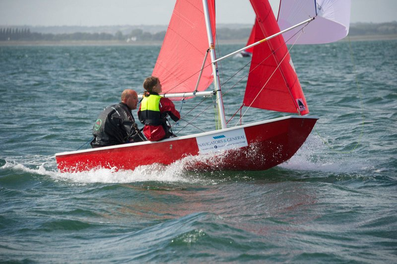 Red Mirror dinghy reaching with spinnaker flying