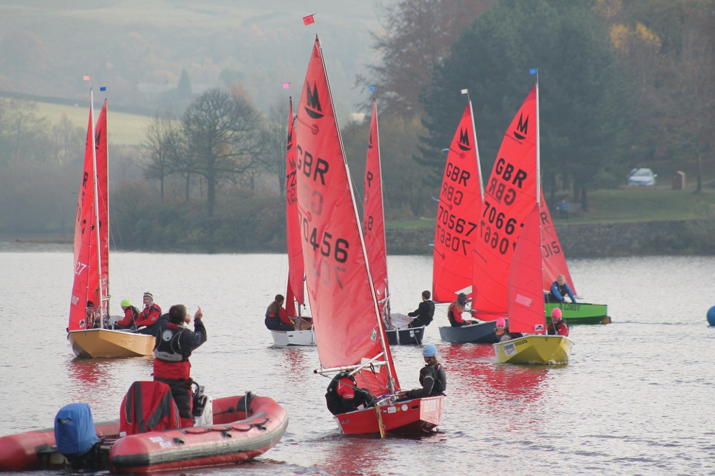 Squad of Mirror dinghies plus coach boat on a lake in a light wind