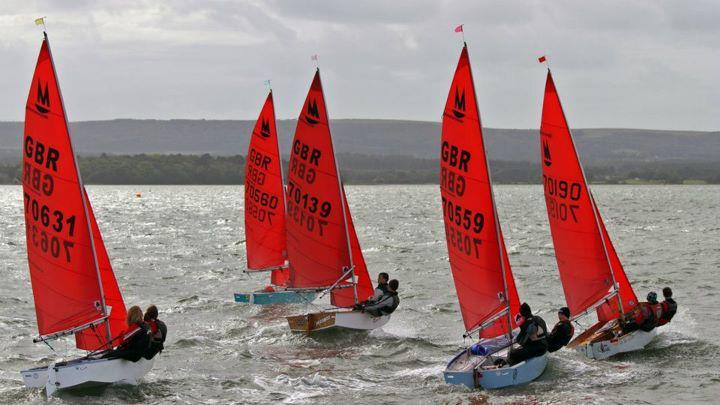 Five Mirror dinghies sailing to windward in a breeze