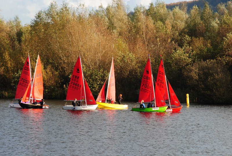 Fleet of Mirror dinghies sailing in a light wind on a sunny day in November