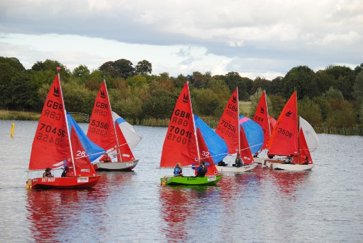 A fleet of 6 Mirrors with spinnakers up on a lake in a light wind