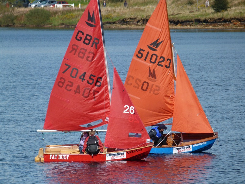 Red Mirror dinghy racing next to an older blue one