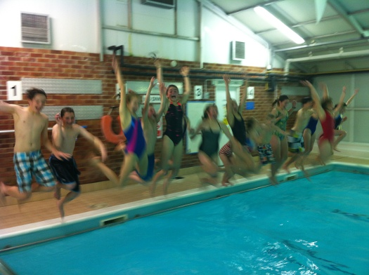 Eighteen children jumping into a swimming pool at once