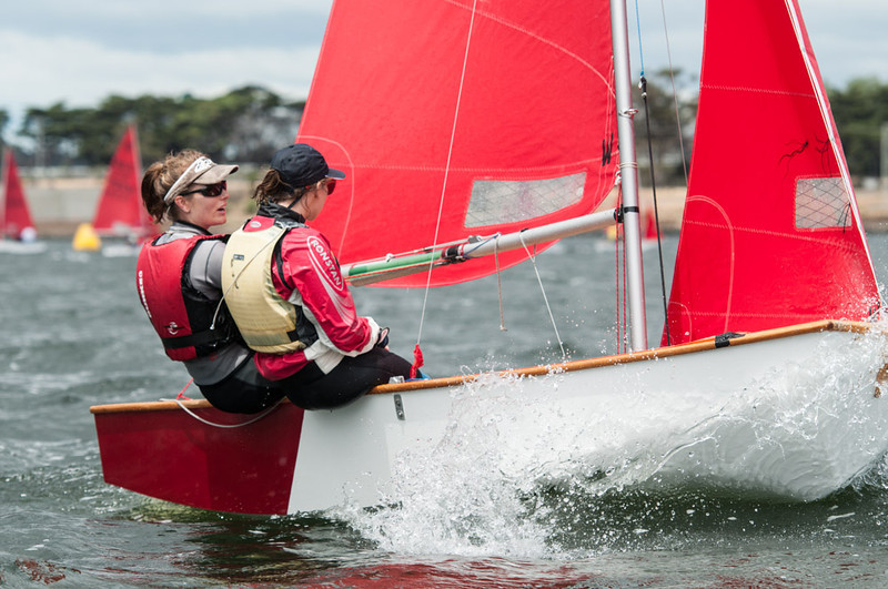 Two girls sailing a red and white Mirror dinghy to windward in choppy conditions