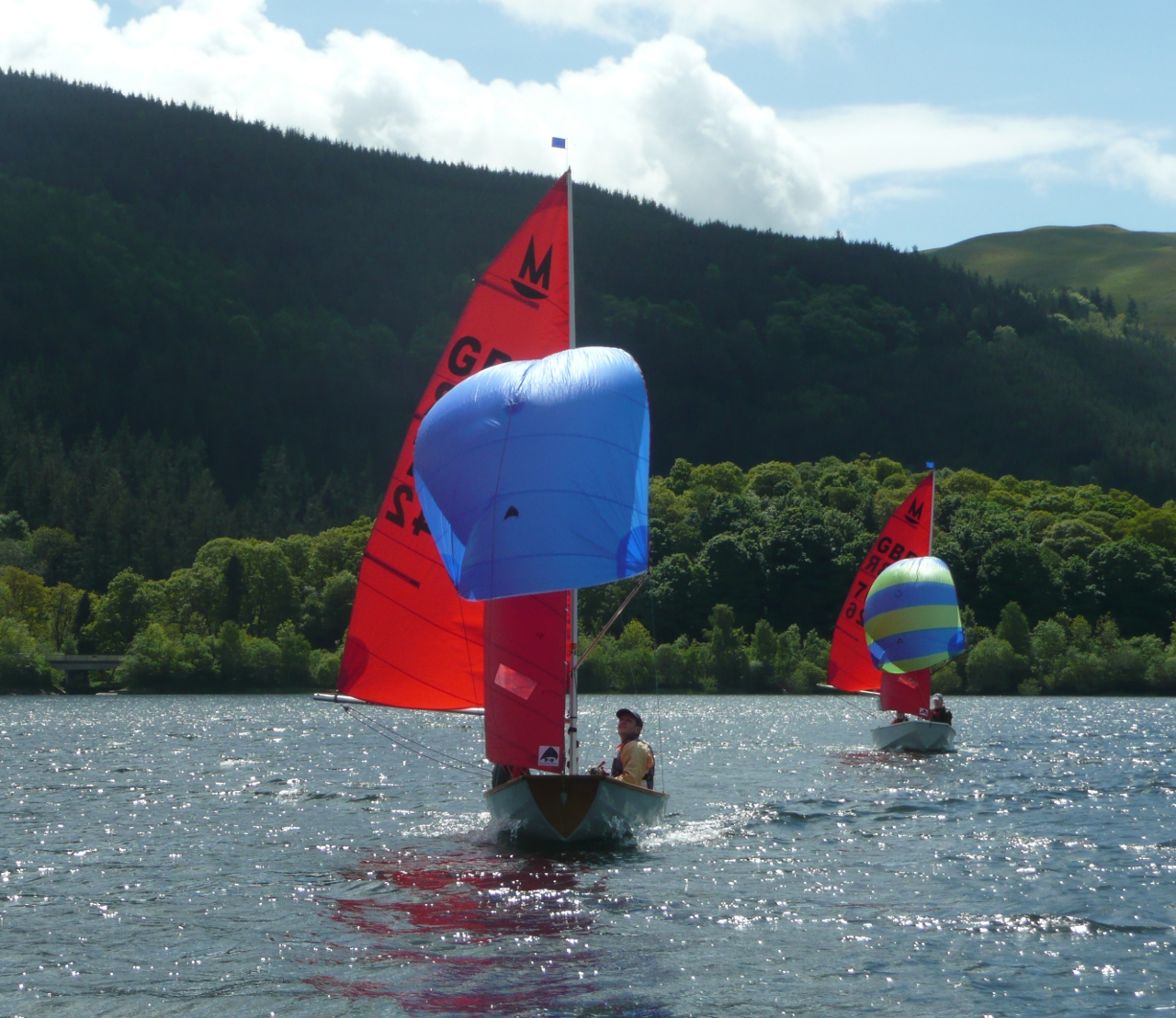 Mirror dinghies, racing on a lake, sailing towards the camera with spinnakers set