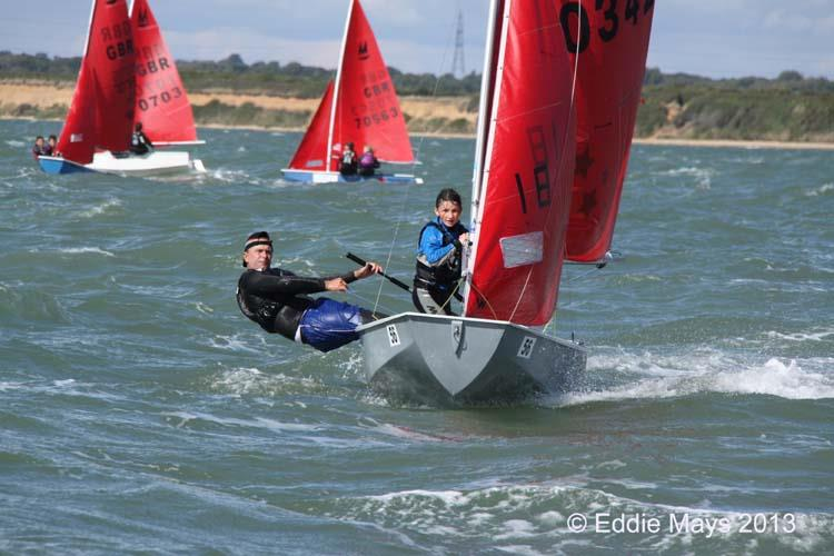 A grey GRP Mirror dinghy sailing towards the camera with the helm hiking hard and the crew setting the spinnaker pole