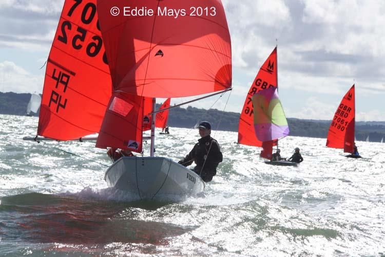 A white GRP Mirror dinghy sailing towards the camera with spinnaker set on a pretty windy day
