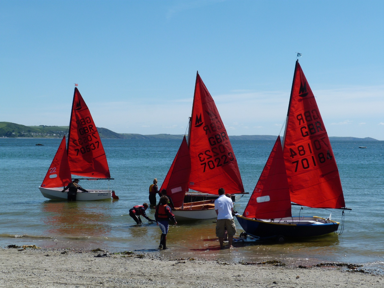 Mirror dinghies launching from a sandy beach onto to a blue sea on a cloudless sunny day