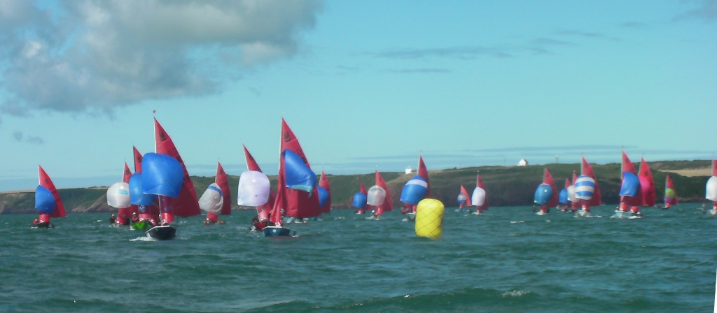 Mirror dinghies running with spinnakers on a sunny day