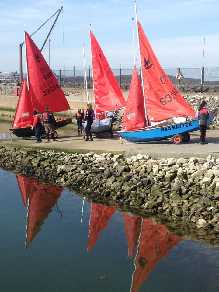 Three Mirror dinghies on a slipway on a calm sunny day