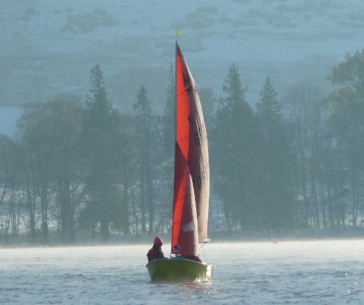 Mirror dinghy sailing on a very cold day with snow on the hills behind