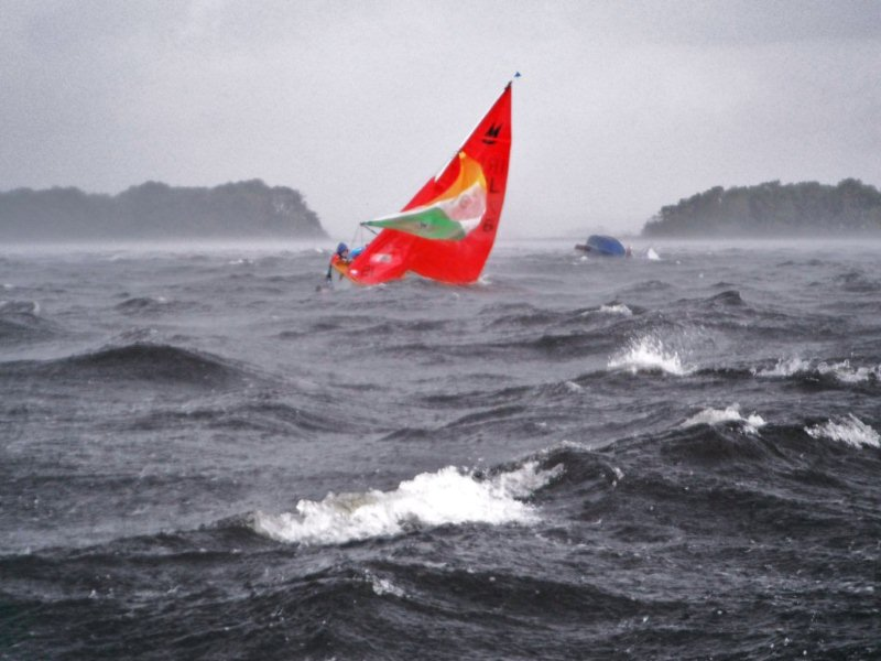 Mirror dinghy from Ireland with tricolour spinnaker flying being righted in the middle of a heavy rain squall