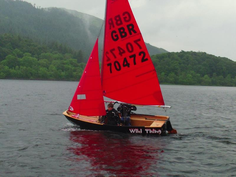 Black wooden Mirror dinghy sailing to windward in a light breeze on a rainy day