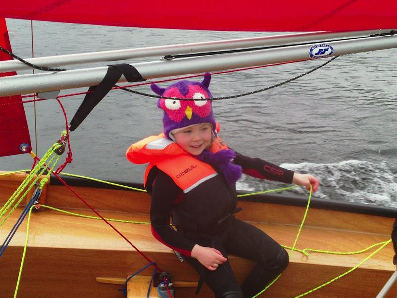 A young girl crewing a Miirror dinghy with lifejacket and owl hat