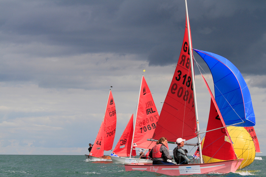 A pink Mirror dinghy flying a blue spinnaker
