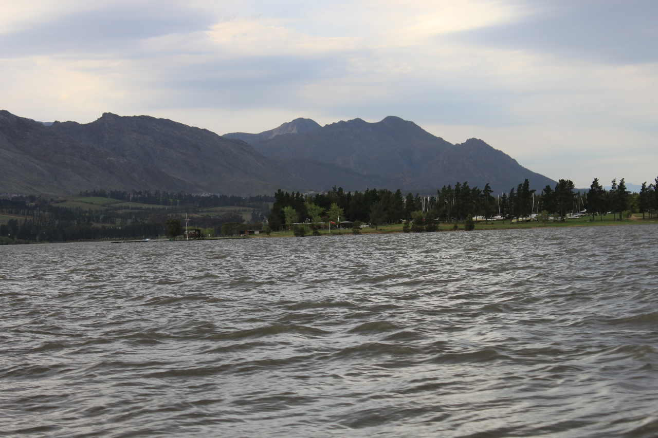A water sports club viewed from the water with mountains in the background