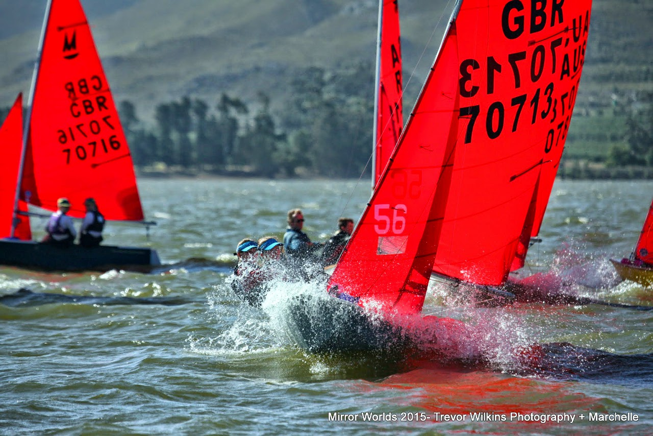 Grey GRP Mirror dinghy with crew sitting out and spray flying