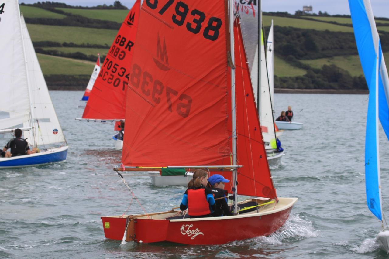 a red GRP Mirror sailing before the start with other boats in the background
