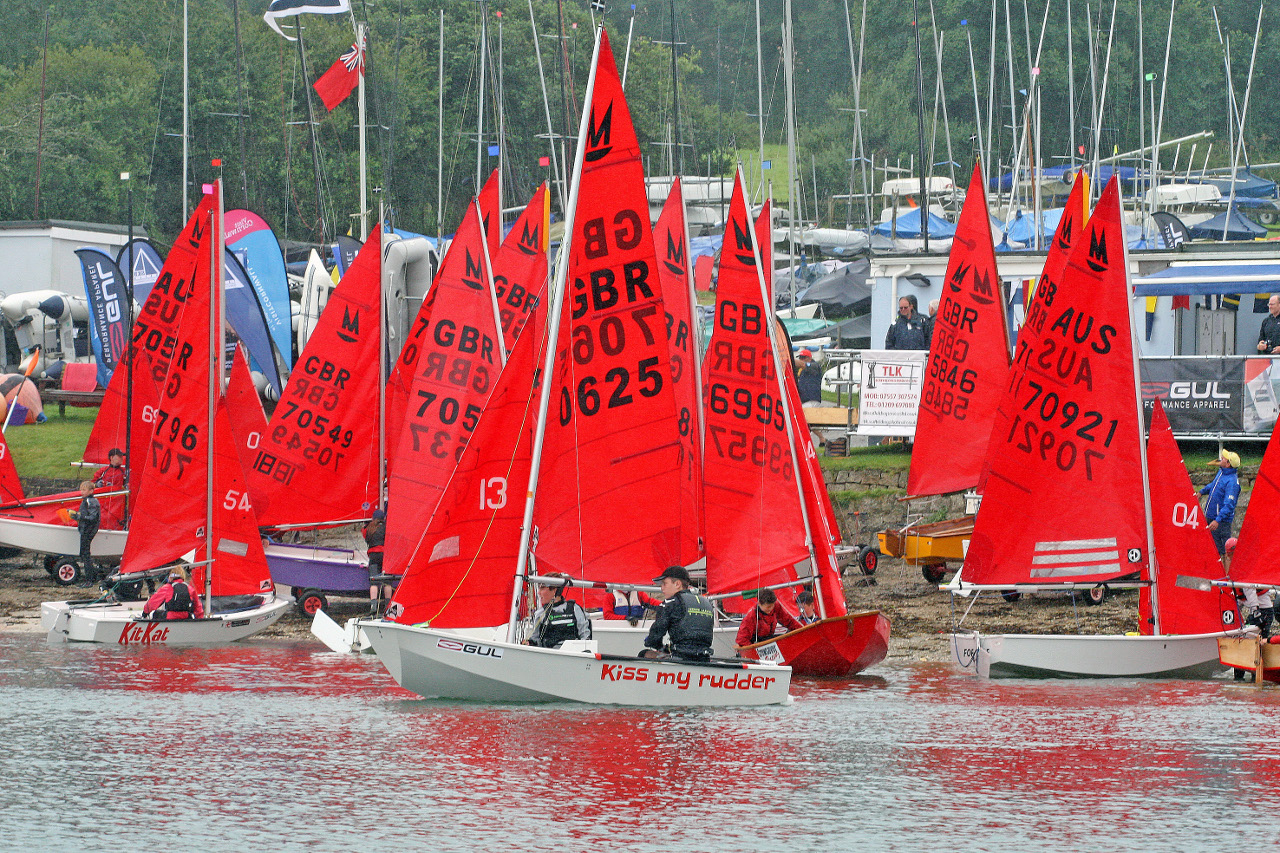 A fleet of Mirror dinghies lauching from a sandy beach with a sailing club in the background