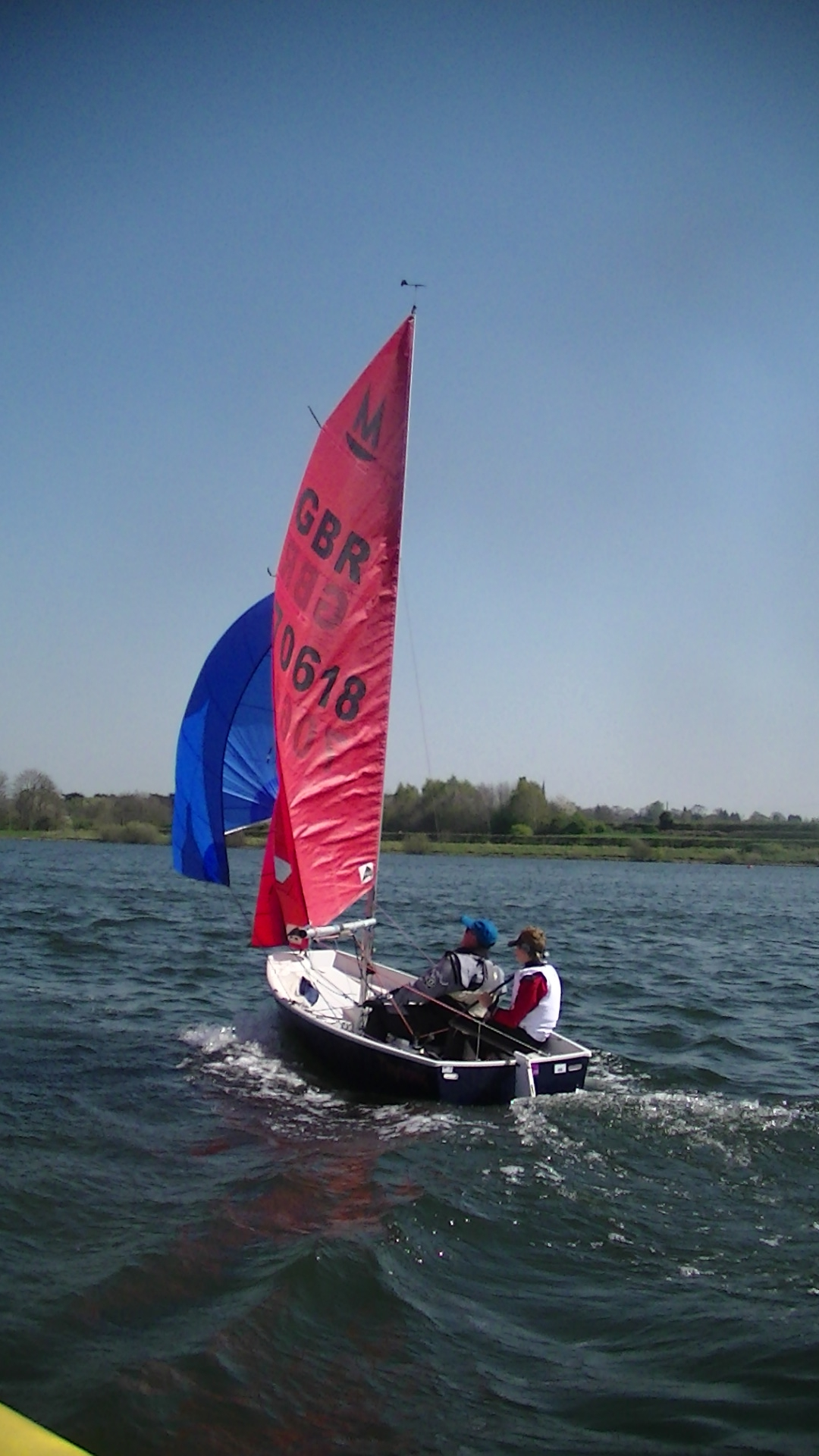 A dark blue GRP Mirror sailing downwind with spinnaker