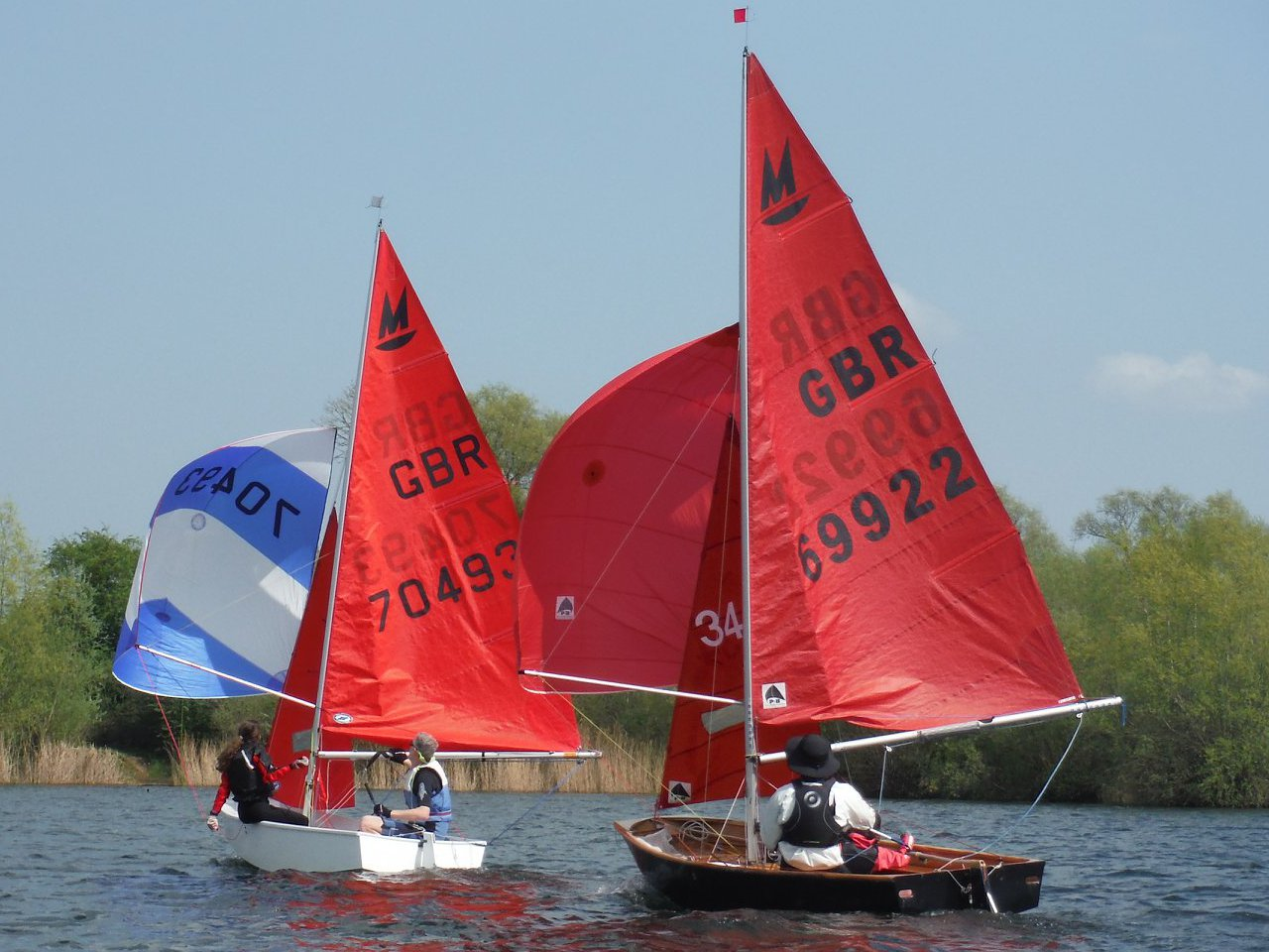 Two Mirror dinghies racing downwind on a lake with spinnakers set