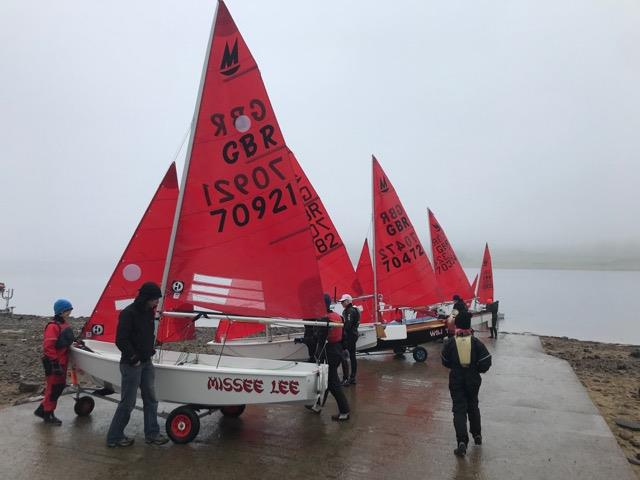 Mirror dinghies launching from a slipway in misty weather