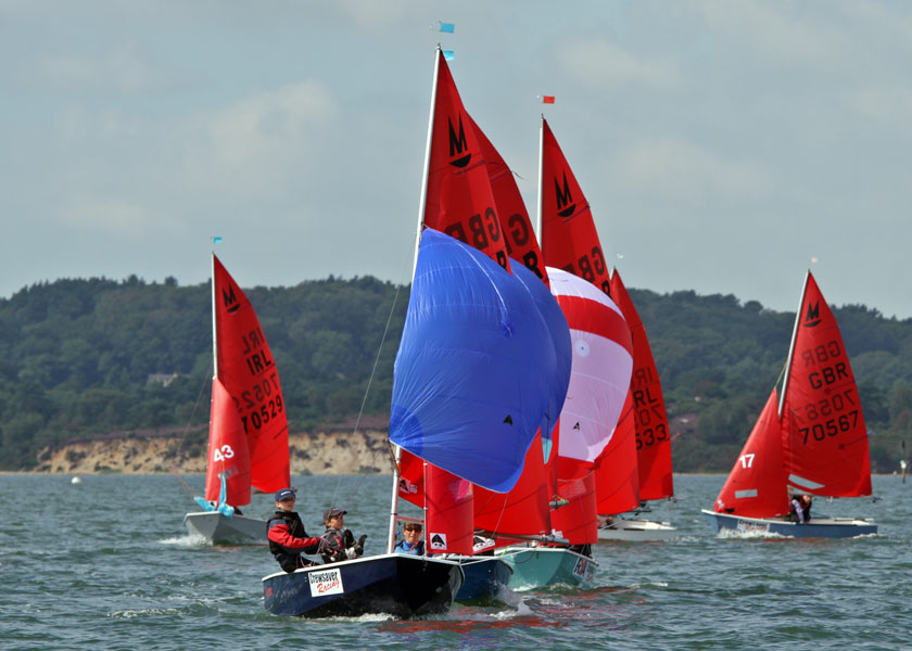 A fleet of Mirrir dinghies racing downwind with spinnakers flying