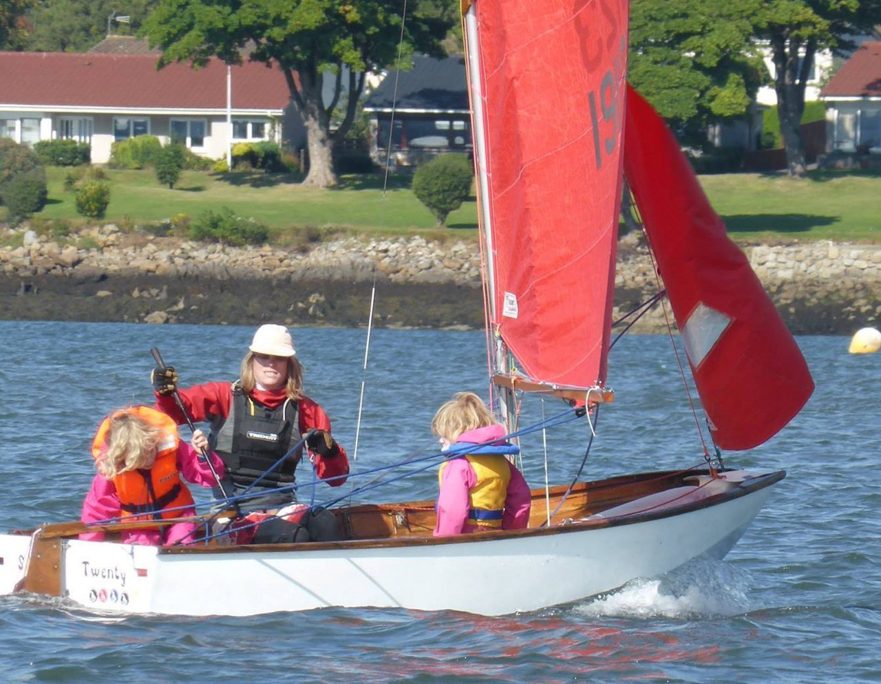 Two children learning how to hold the tiller extension in a Mirror Dinghy
