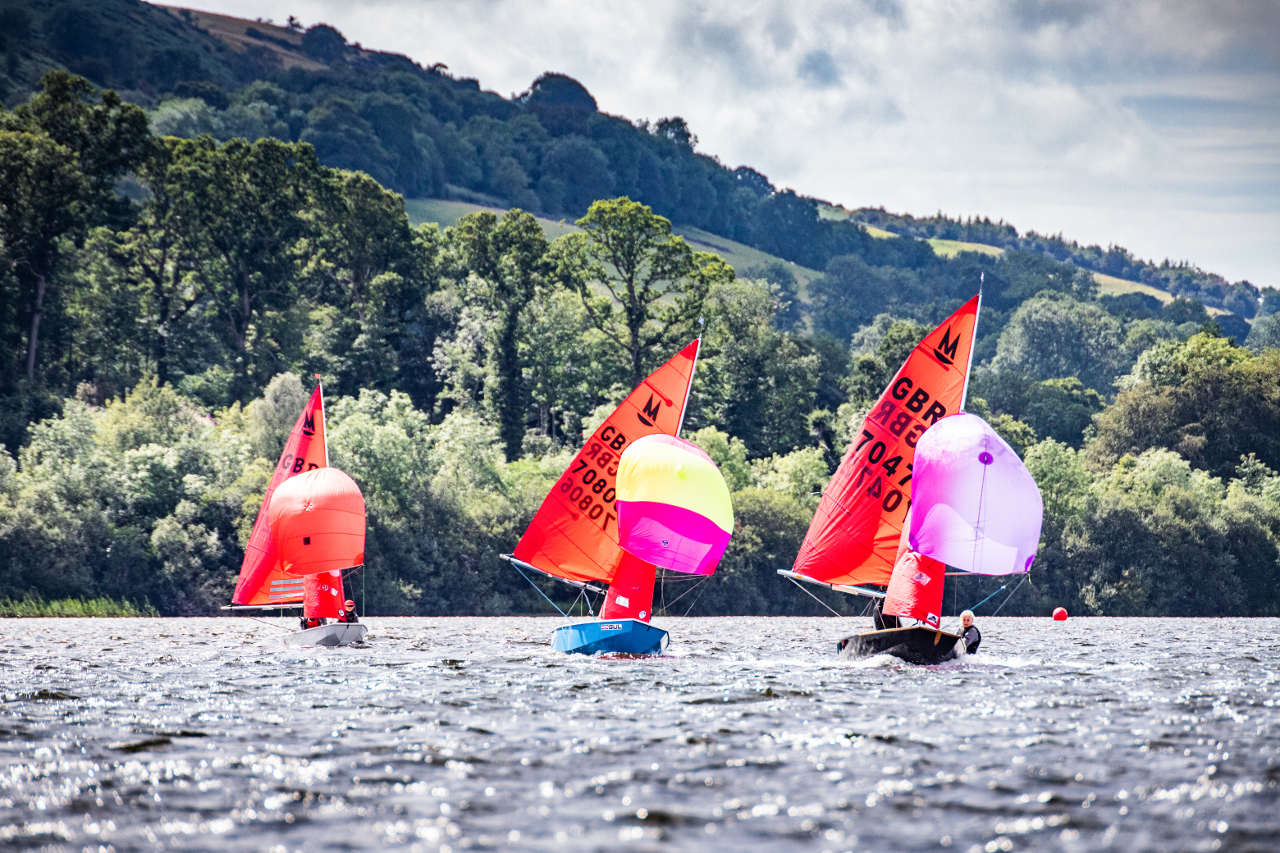 Three Mirrors racing downwind with spinnakers set and some hills of the Lake District in the background