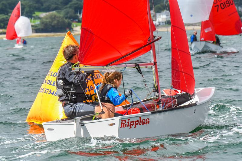 A white GRP Mirror dinghy called 'Ripples' sailing to windward having just rounded the leeward mark