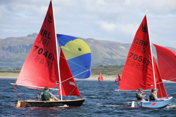 Two Mirror dinghies racing on a reach with spinnakers set with mountains of Sligo in the background