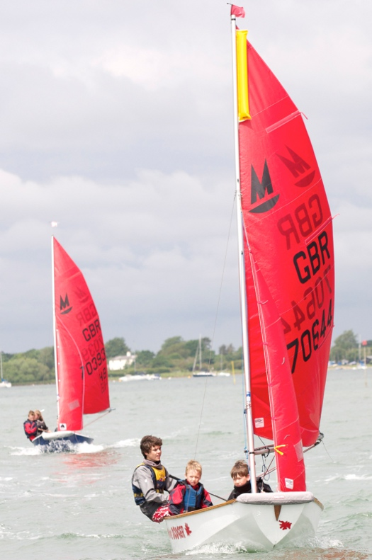 Mirror dinghy with a yellow inflated float at the top of the mainsail