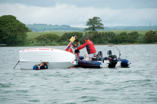Mirror dinghy capsized with two small children righting it with a RIB assisting