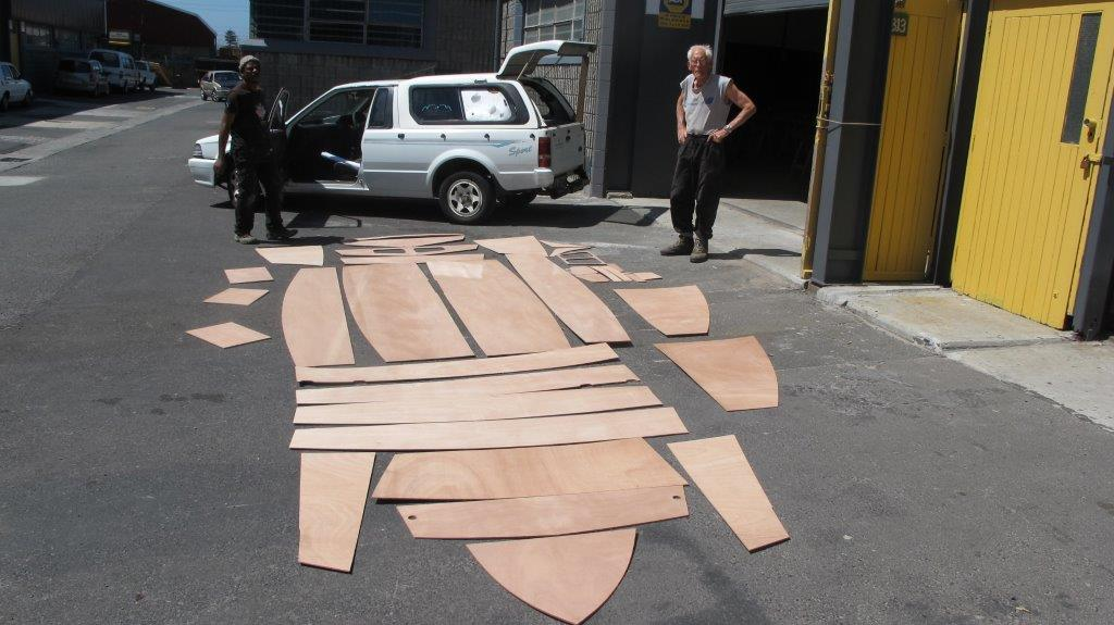 A kit of wooden plywood parts for a Mirror dinghy laid out in a car park