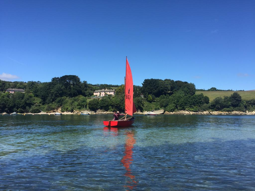 A red wooden Mirror dinghy sailing in inlet of the Carrick Roads on a sunny day